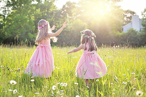 twin girls playing around on the grass